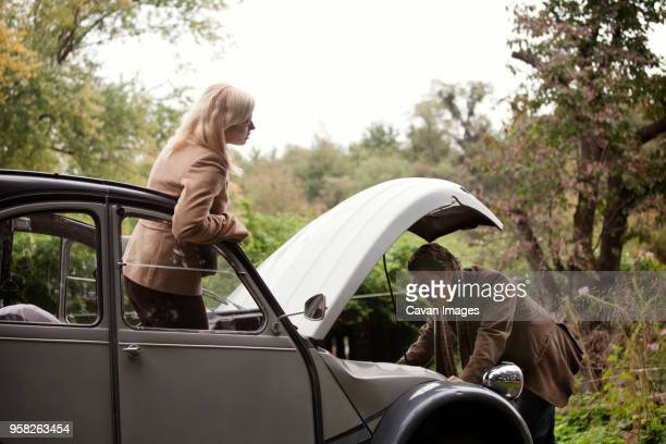 woman looking at man repairing vintage car - vintage auto repair stock pictures, royalty-free photos & images