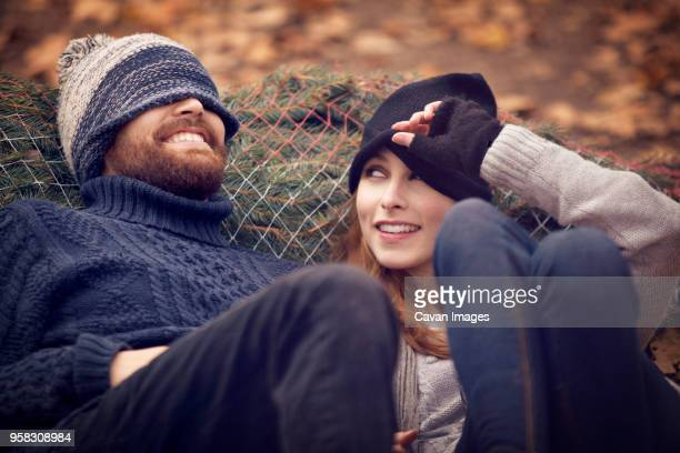 Woman looking at man wearing knit hat while leaning on Christmas Tree