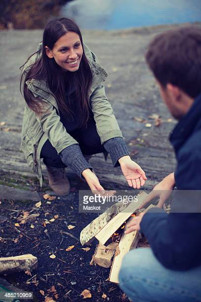 Woman looking at man while sitting by campfire