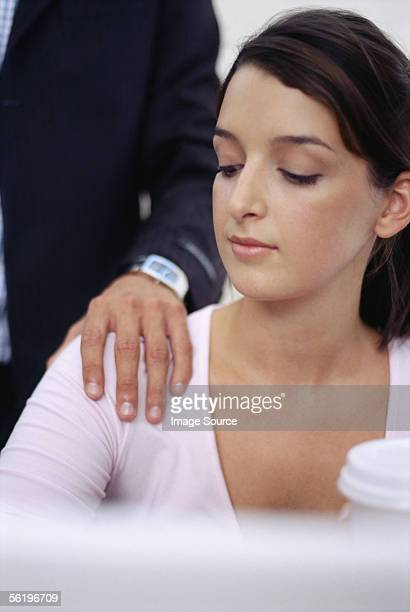 Woman looking at man's hand on her shoulder