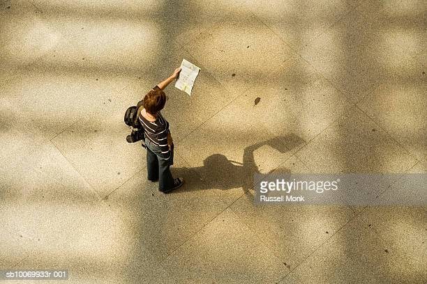 Woman looking at map in train station, high angle view