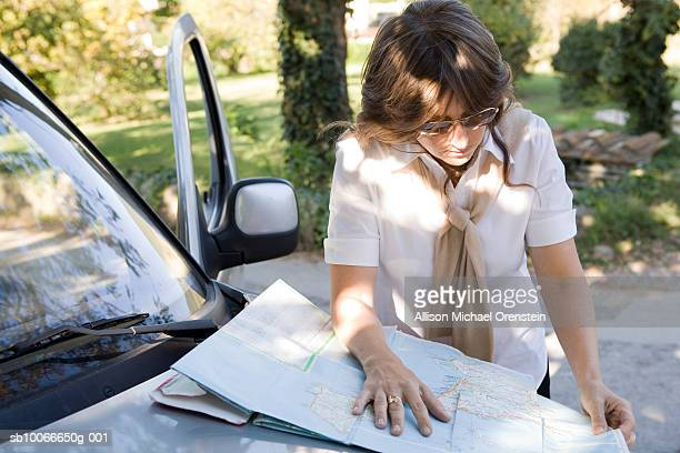 woman looking at map on hood of car - allison michael orenstein stock pictures, royalty-free photos & images