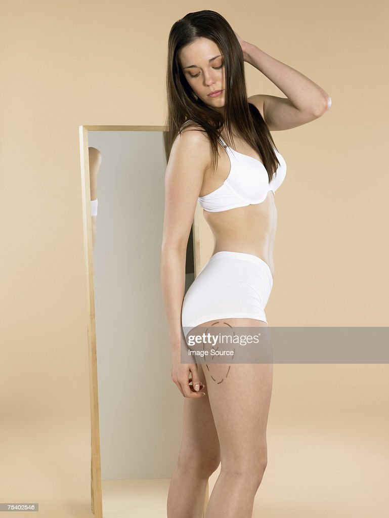Woman looking at mark on her leg : Stock Photo