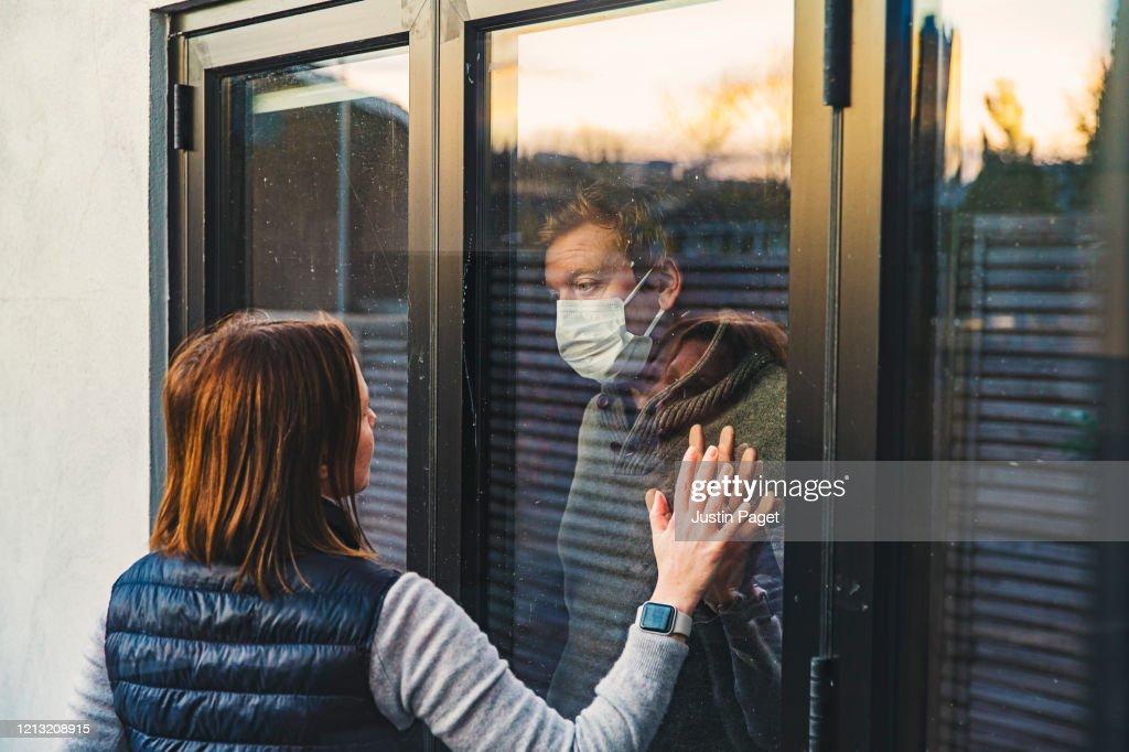 Woman looking at masked husband quarantined behind window : Foto stock