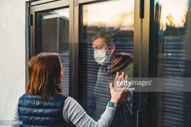 woman looking at masked husband quarantined behind window - social distancing stock-fotos und bilder
