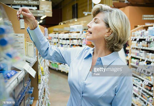 Woman Looking at Medicines at Health Food Store