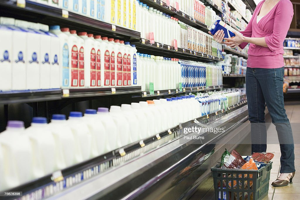 Woman looking at milk carton in supermarket, low section : Stock Photo