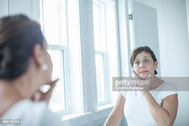 Woman looking at mirror in bathroom