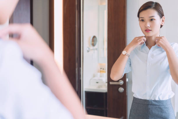woman looking at mirror in the bathroom - preparation stock pictures, royalty-free photos & images