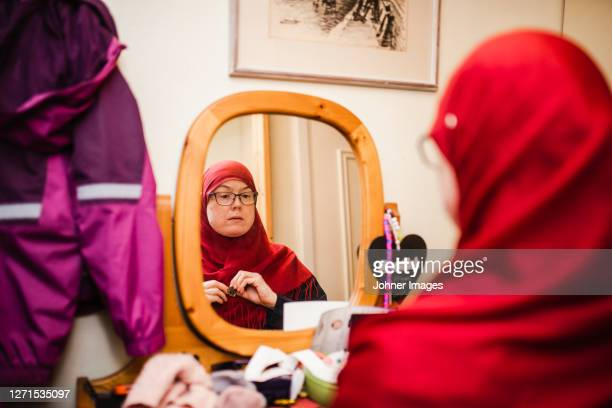 woman looking at mirror - västra götaland county stock pictures, royalty-free photos & images