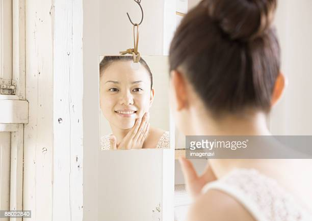 A woman looking at mirror