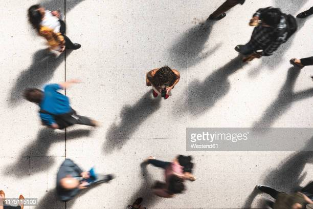 woman looking at mobile phone in between hurrying people, top view - 背景に人 ストックフォトと画像