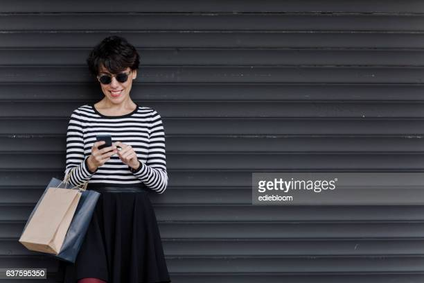 woman looking at mobile phone with shopping bags