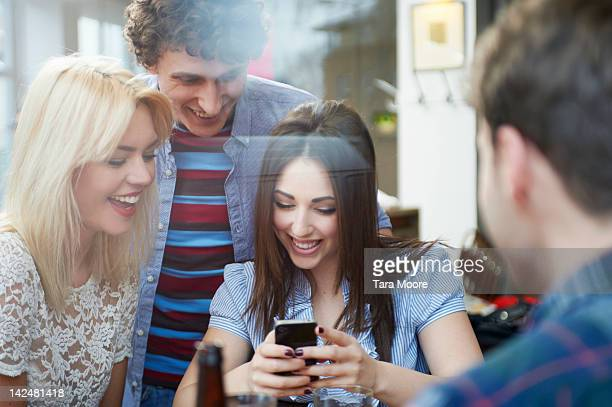 woman looking at mobile with friends in restaurant - newtechnology stock pictures, royalty-free photos & images