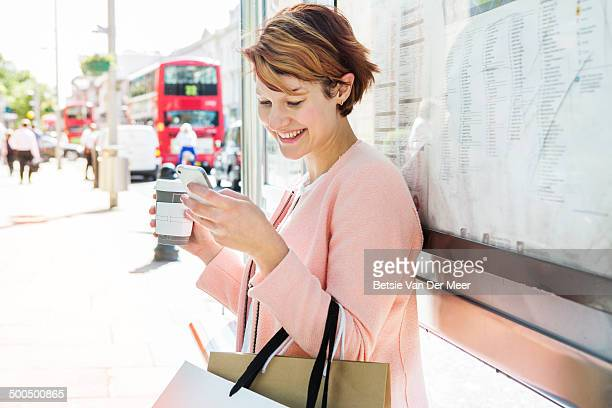 woman looking at mobilephone at bus stop.