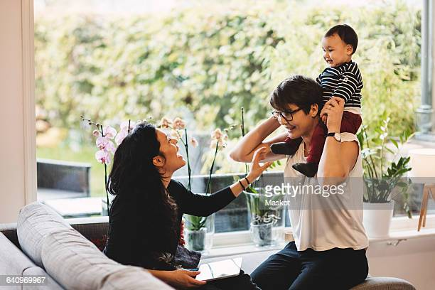 Woman looking at mother carrying daughter on shoulder by window