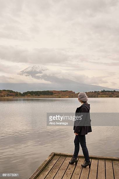 a woman looking at mount fuji - akio iwanaga ストックフォトと画像