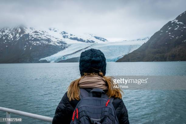 woman looking at mountain range and glacier. - cruise vacation stock pictures, royalty-free photos & images