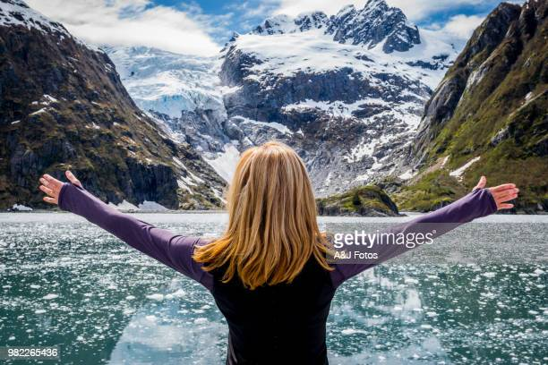 woman looking at mountain range and glacier - alaska stock pictures, royalty-free photos & images