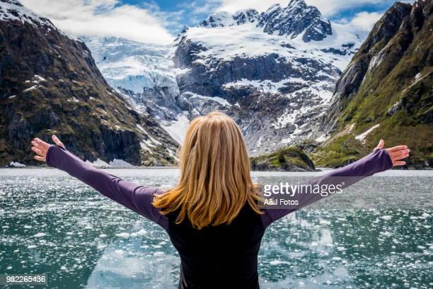 Woman looking at mountain range and glacier