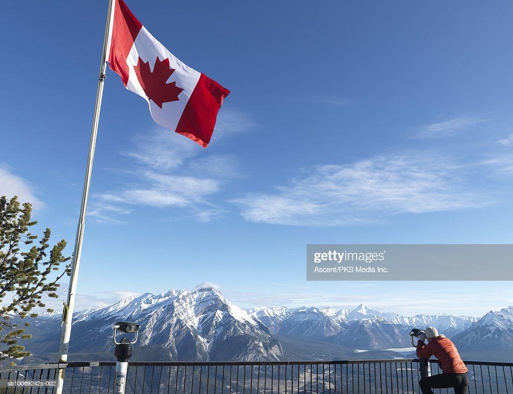 Woman looking at mountain range through coin operated binoculars, Canadian flag blowing beside, rear view : Stockfoto