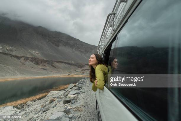 woman looking at mountains of northern pakistan from window in the van - pakistan stock pictures, royalty-free photos & images