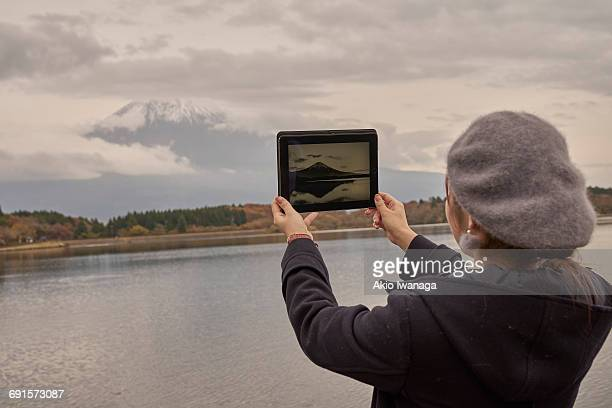 a woman looking at mt. fuji on a tablet - akio iwanaga ストックフォトと画像