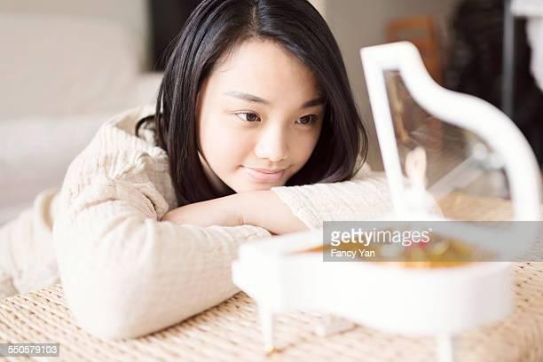 woman looking at music box and visioning
