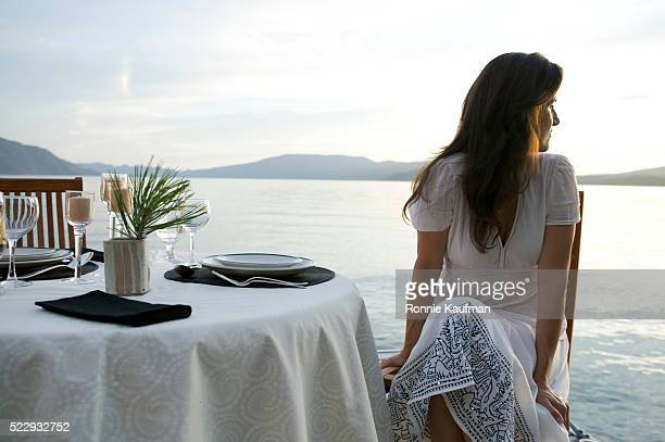 Woman Looking at Ocean from Dining Table
