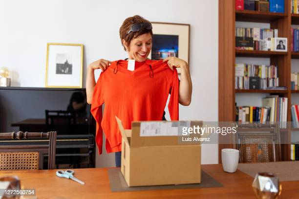 woman looking at online purchased clothing at home - top garment stock pictures, royalty-free photos & images