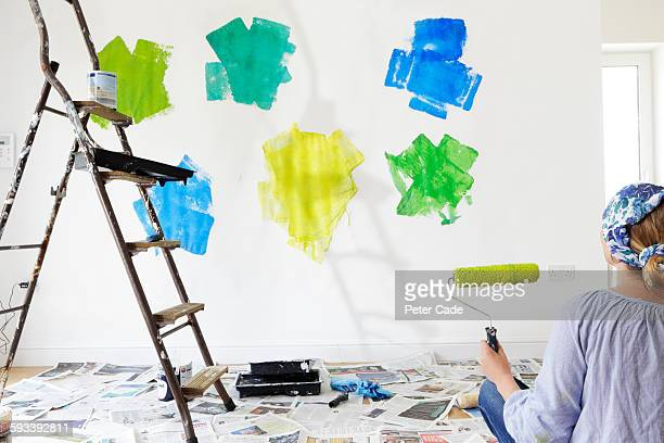 Woman looking at paint choices on wall