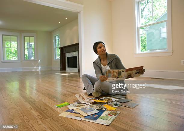 woman looking at paint samples in empty room - women wearing nothing stock photos and pictures