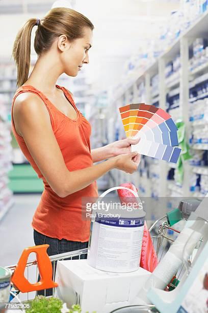 Mujer mirando en las muestras de pintura en la tienda