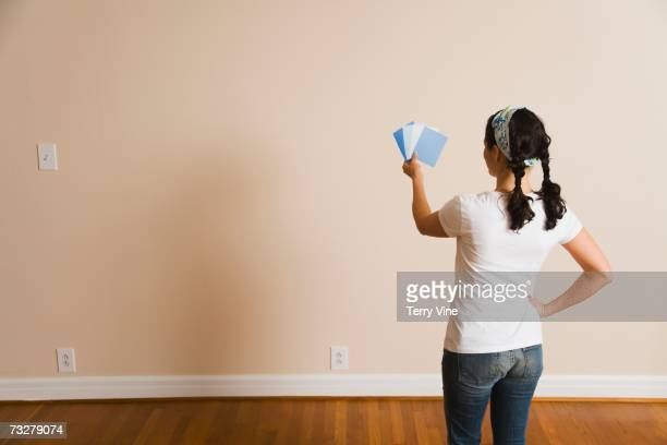 Woman looking at paint swatches in front of bare wall
