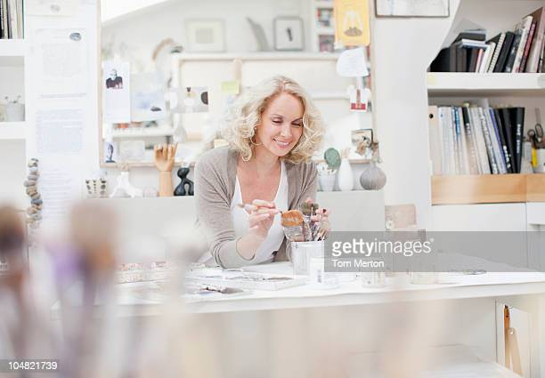 Woman looking at paintbrushes in art studio
