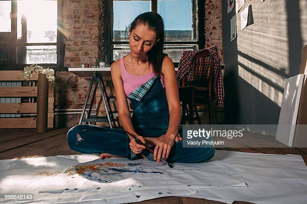 Woman looking at painting while sitting on floor in art studio
