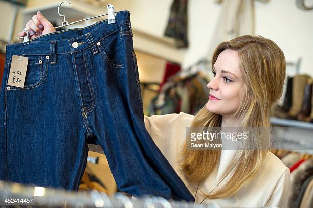 woman looking at pair of jeans - sean malyon stock pictures, royalty-free photos & images