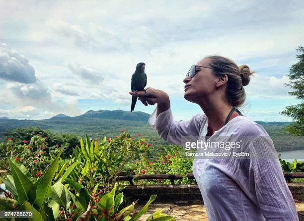 Woman Looking At Parrot Perching On Her Hand