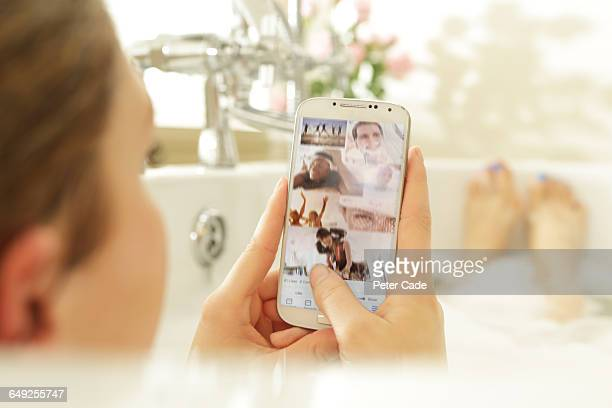 Woman looking at phone in bath