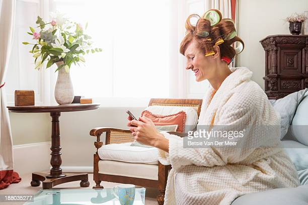 Woman looking at phone, sitting with rollers in ha