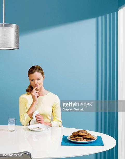Woman looking at plate of cookies