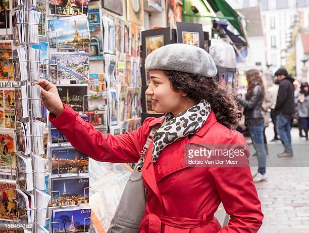 Woman looking at postcards at Montmartre, Paris.