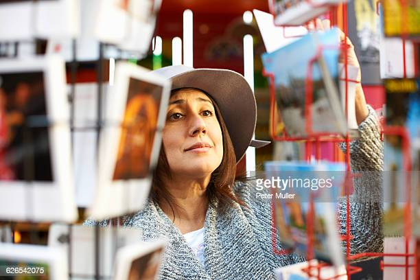 Woman looking at postcards in shop