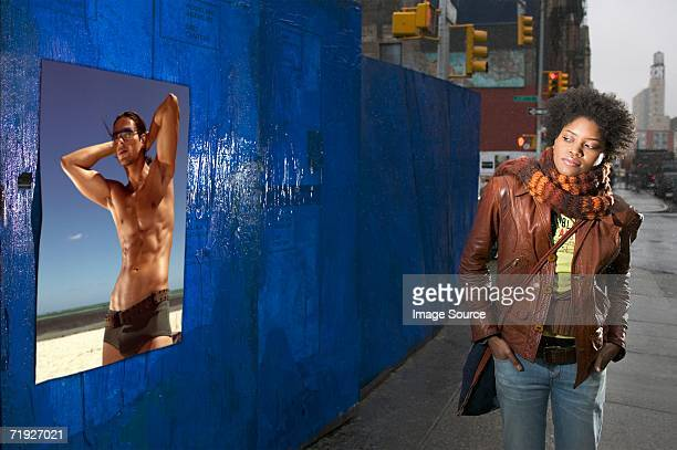 Woman looking at poster of bare chested man