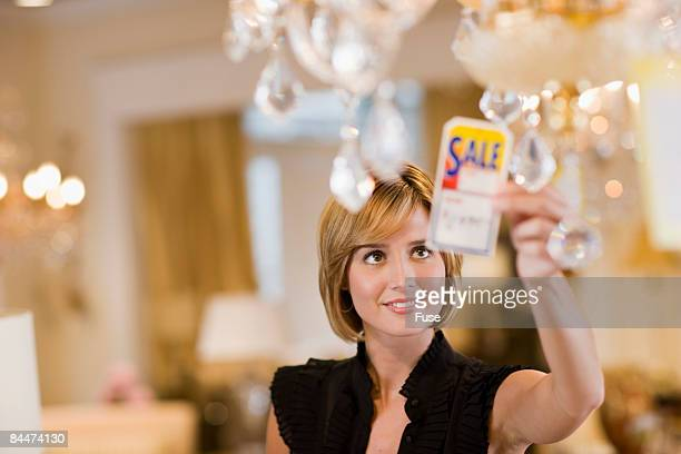 Woman Looking at Pricetag on Chandelier