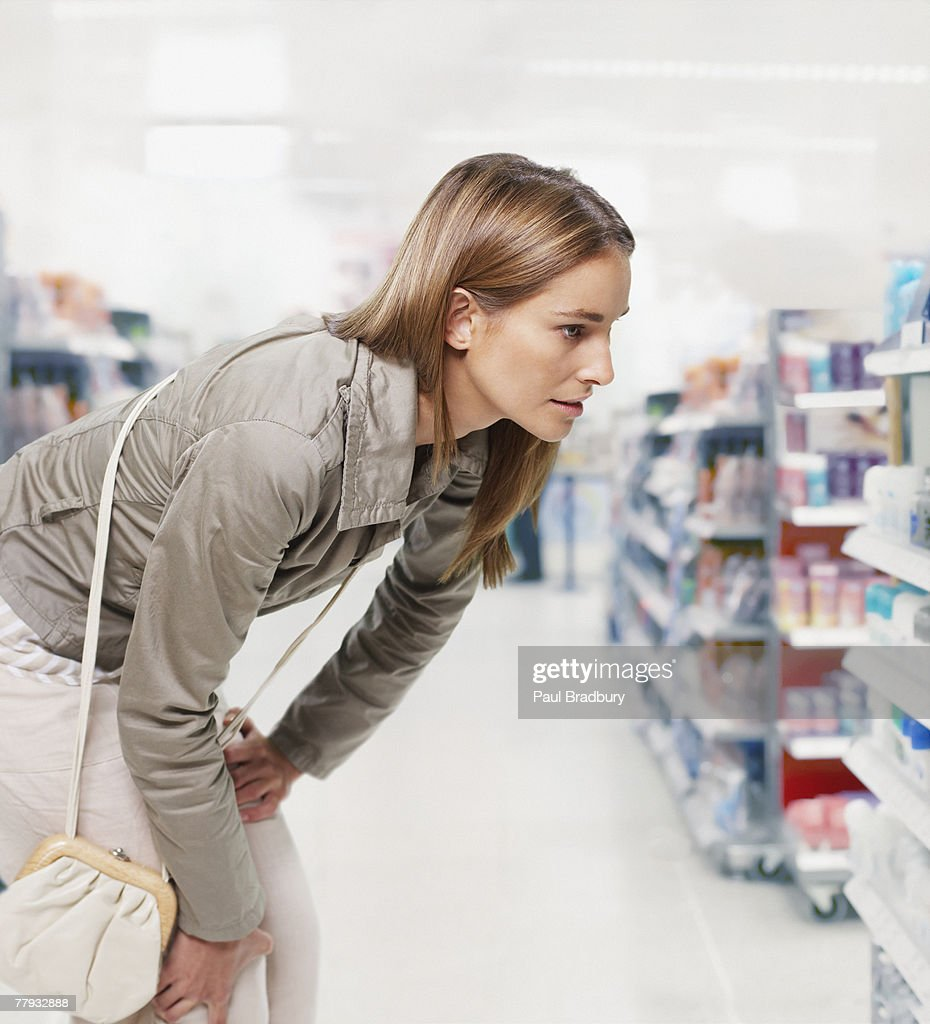 Woman looking at products in a pharmacy : Stock Photo