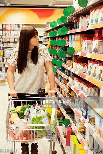 Woman looking at products while shopping in supermarket