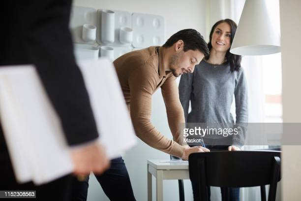 woman looking at real estate agent while man signing documents at new home - näringsliv och industri bildbanksfoton och bilder