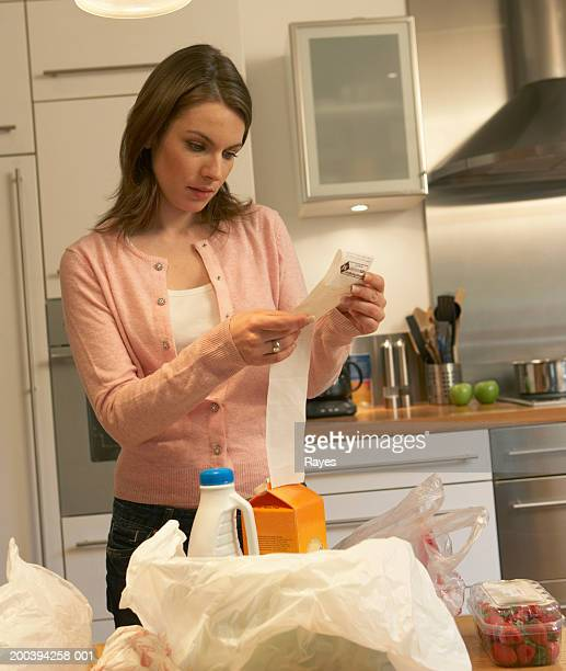 woman looking at receipt in kitchen - milk carton stock photos and pictures