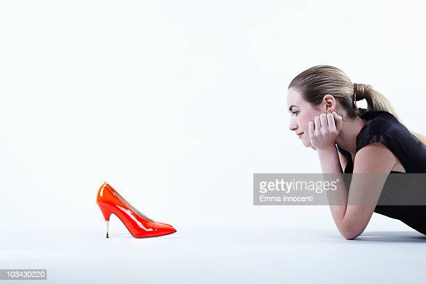 woman looking at red shoes